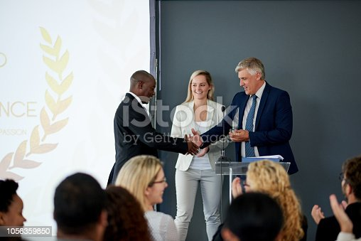 Shot of a young businessman being awarded a prize during an awards giving ceremony at a conference