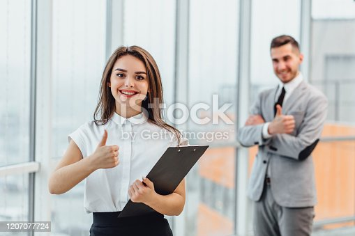 488279375 istock photo Well Done Pretty woman on the forefront and blurred man on the background giving thumbs up, saying that the goal is successfully achieved. 1207077724