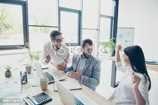istock Well done! Success and team work concept. Three business partners are amazed about great news, sitting at the work places next to each other in a row, dressed by the office dress code 936273678