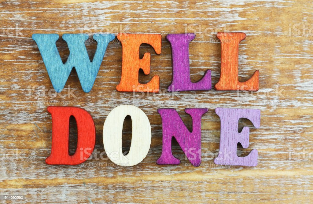 Well done written with colorful wooden letters on rustic wooden surface stock photo