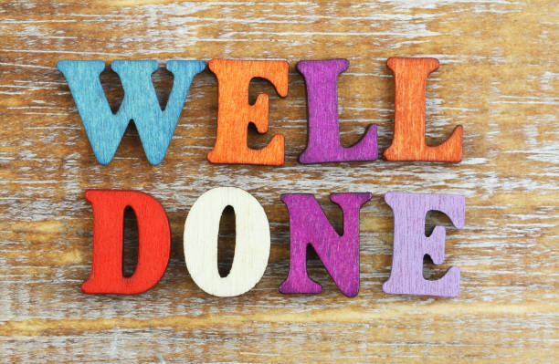 well done written with colorful wooden letters on rustic wooden surface - well done stock photos and pictures