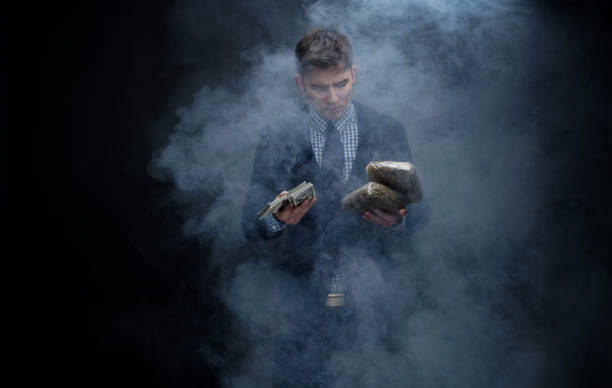 well dressed businessman holding a brick of weed and cash - money black background stock photos and pictures