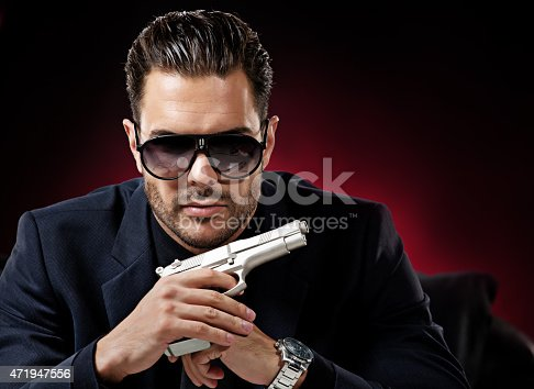 471947536 istock photo well dressed man holding gun 471947556