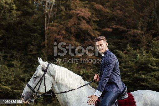 Handsome well dressed man riding horse