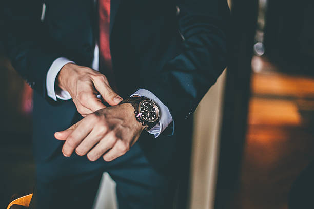 Well Dressed Man putting his wrist watch Well Dressed Man putting his wrist watch grace stock pictures, royalty-free photos & images