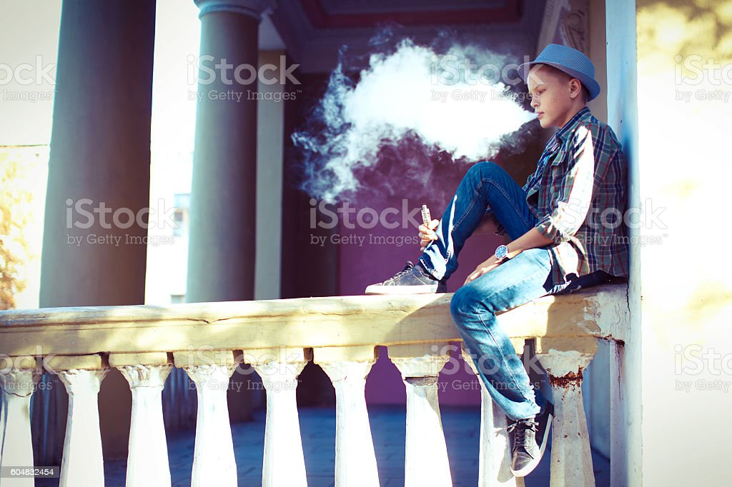 Well dressed man smoking sitting on a street sidewalk stock photo