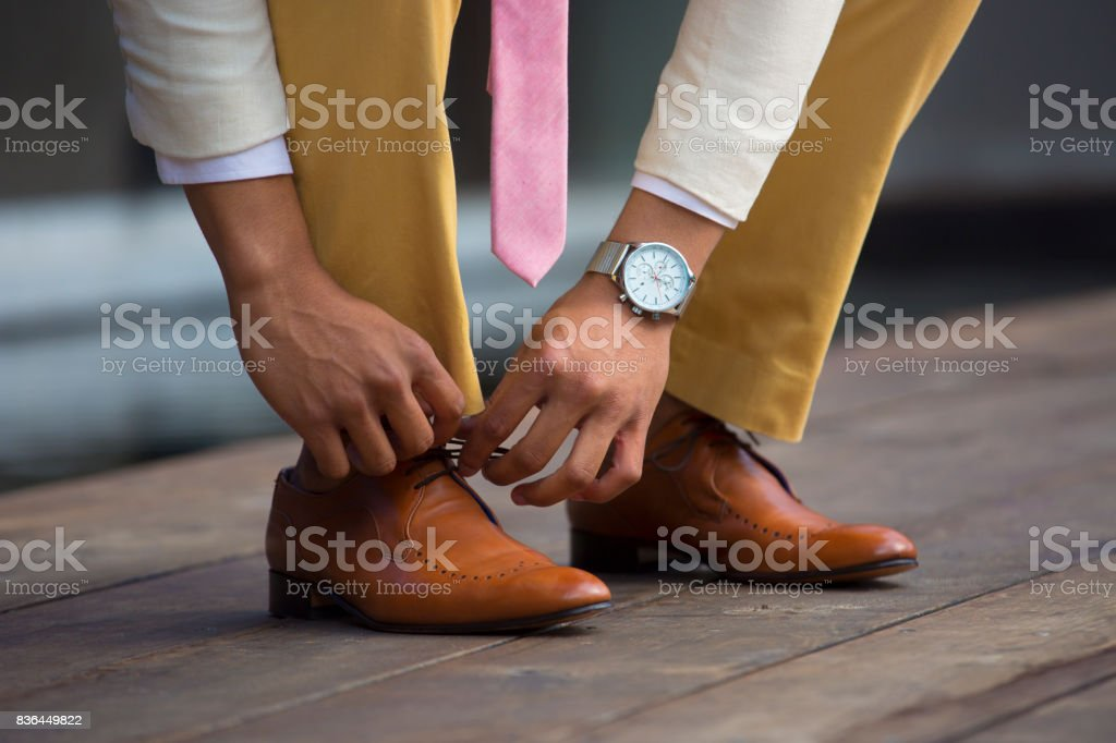 Well dressed man ties his brown leather shoe lace stock photo