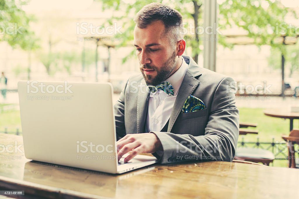 A well dressed man working on his laptop on a bench stock photo