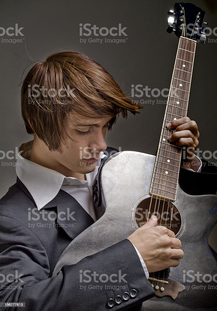 Well Dressed Young Man Playing the Guitar royalty-free stock photo