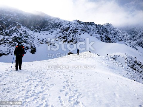 istock Well Equipped Hiker walking on a huge blanket of snow to reach top of the Indian Himalayan Mountain. 1271513585