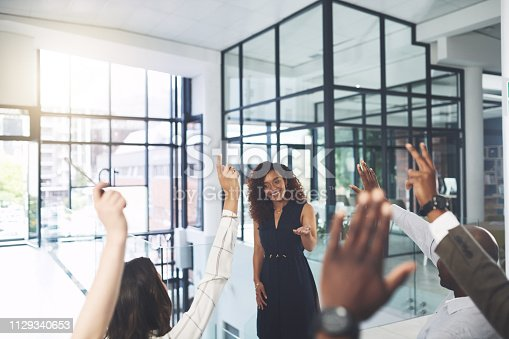 Closeup shot of a group of businesspeople raising their hands during a presentation in an office