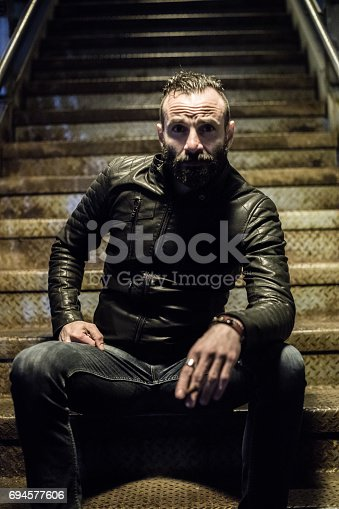 istock A bearded, white male, lights a cigarette in the streets of