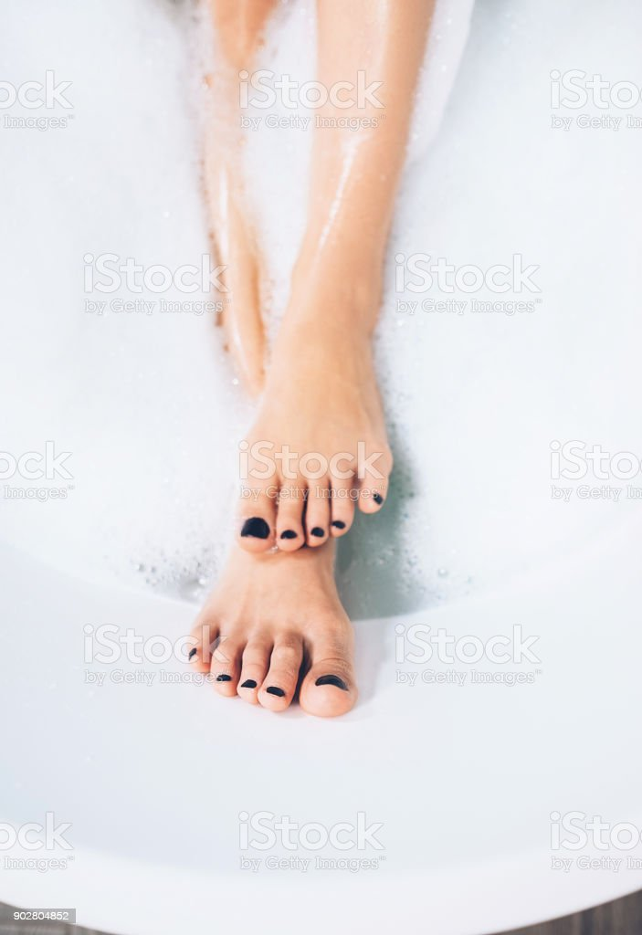well groomed woman's legs with black pedicure in bathtub stock photo