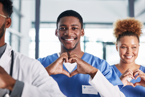 Portrait of a group of medical practitioners making a heart shape with their hands in a hospital