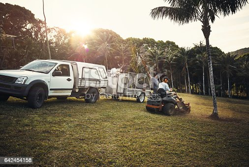 Shot of two landscapers working together in a park