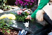 Woman's hand putting some flowers on the grave. There is also a little white angel sculpture on the gravestone.