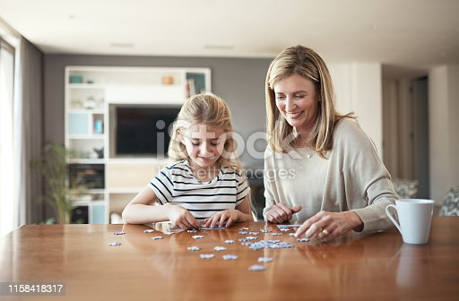 Cropped shot of an attractive mature woman and her granddaughter building a puzzle in the dining room at home