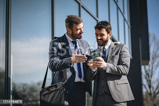 Smiling modern adult businessman reading an e-mail at his phone about his promotion to CEO and showing that to his colleague