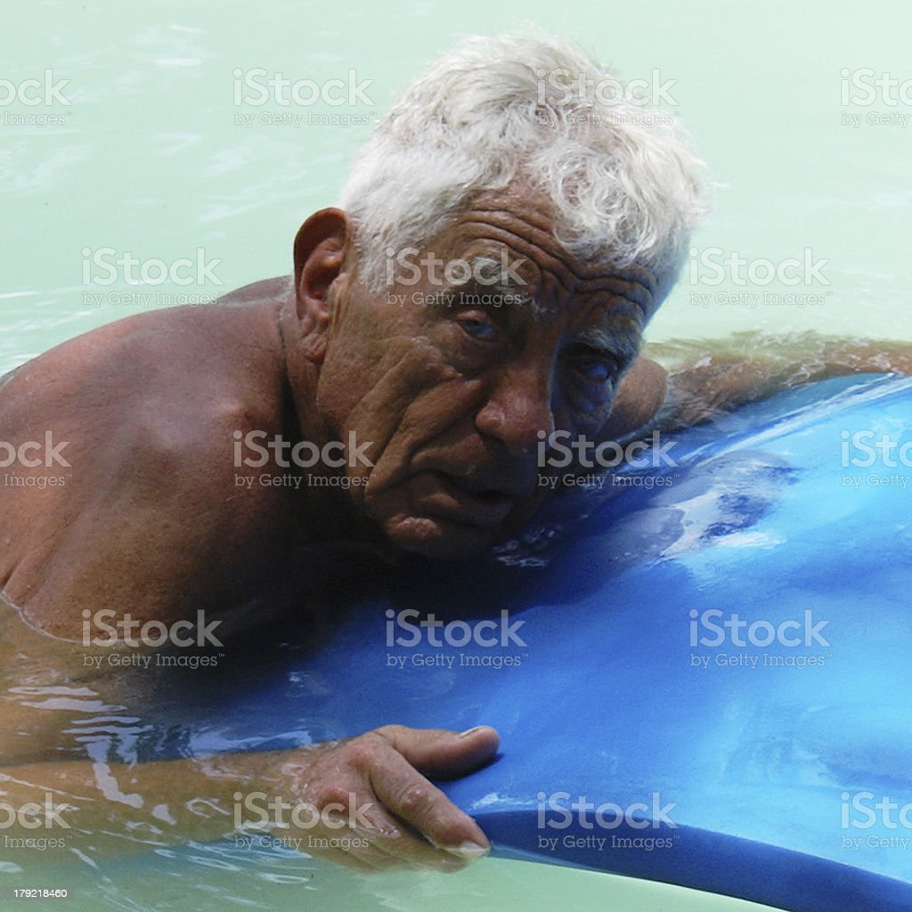 Well tanned senior with float in pool royalty-free stock photo