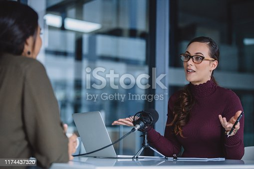 Cropped shot of an attractive young businesswoman sitting in her office and being interviewed during a broadcasting