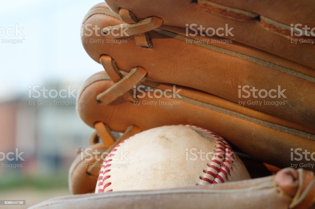 Well used baseball and a glove in a baseball field stock photo