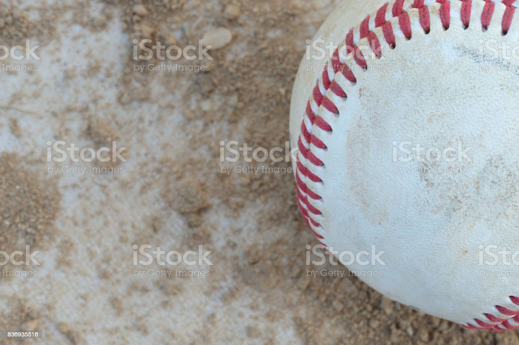 Well used baseball in a sandy baseball field stock photo