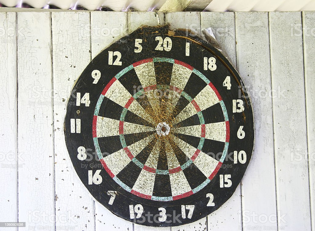 Well used dartboard hanging in a shed royalty-free stock photo