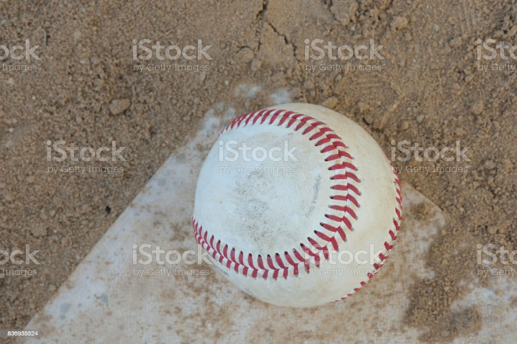 Well worn baseball sits at home plate in the sand and dirt stock photo