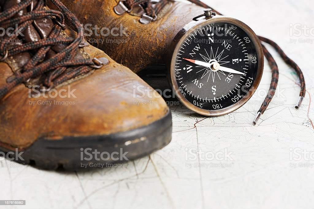 Well worn hiking boots with map and compass royalty-free stock photo