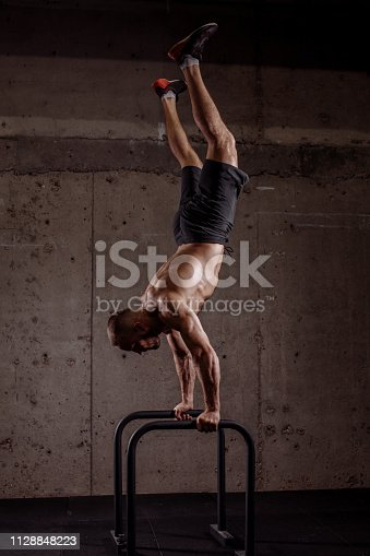 well-built gymnast performing on parallel bars. full length photo. coordination and wellness concept