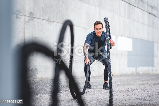 Low angle viewpoint of crouching Caucasian athlete in good condition using battle ropes in alternating wave movement outdoors.