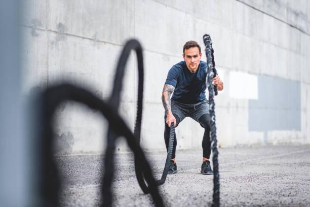 Gut konditionierte männliche Athleten mit Kampfseilen im Freien – Foto