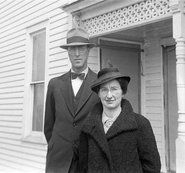 well-dressed couple in coats and hats 1941, retro Well-dressed couple in 1941 he in suit, she in lambskin coat. Wellman, Iowa. Scanned film with grain. war effort stock pictures, royalty-free photos & images