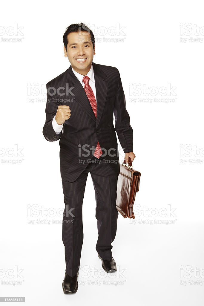 Well-dressed Indian businessman with briefcase clenches his fist expressing success royalty-free stock photo