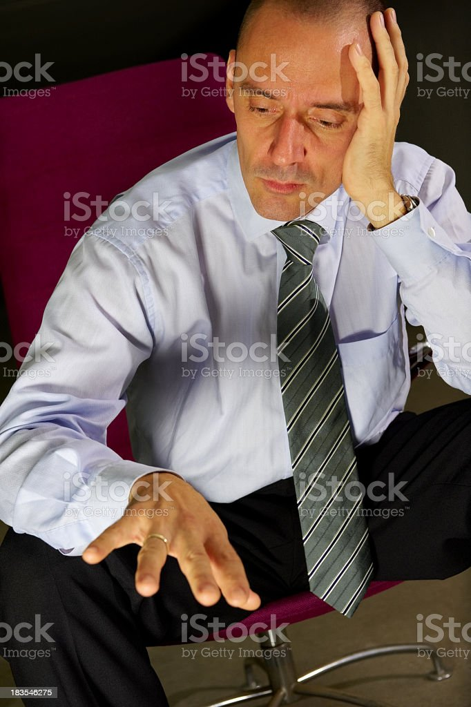 Welldressed man in chair looking sadly at his ring Adult business man with problems in his marriage looking at his ring with his head in his hand. Adult Stock Photo
