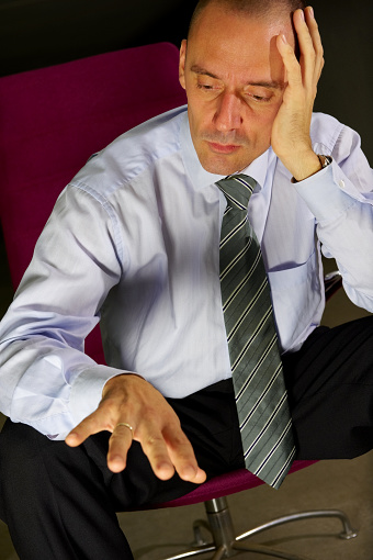 Welldressed Man In Chair Looking Sadly At His Ring Stock Photo - Download Image Now