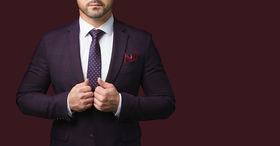 Sharp dressed man in jacket and tie isolated on dark red background. Picture for advertising a men's clothing store. A symbol of success and masculinity