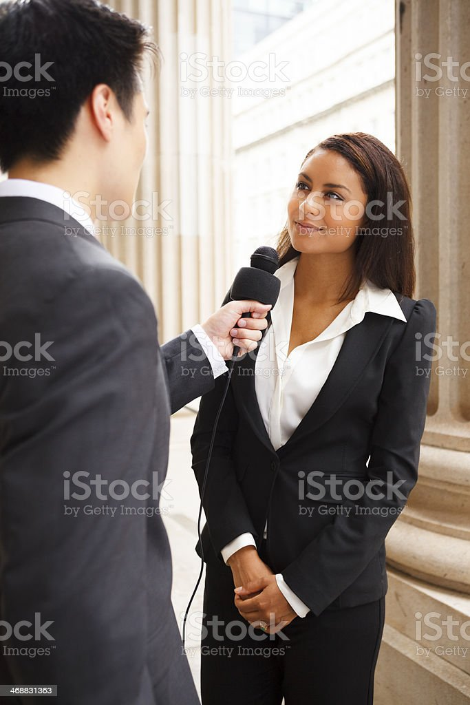 Well-dressed man with mic interviewing well-dressed woman royalty-free stock photo