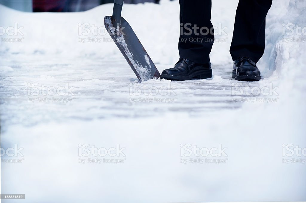 Welldressed man with snow shovel and copyspace stock photo