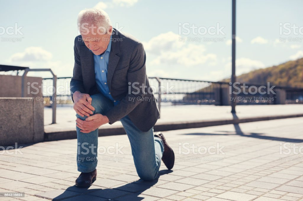 Well-dressed senior man feeling his knee after falling stock photo