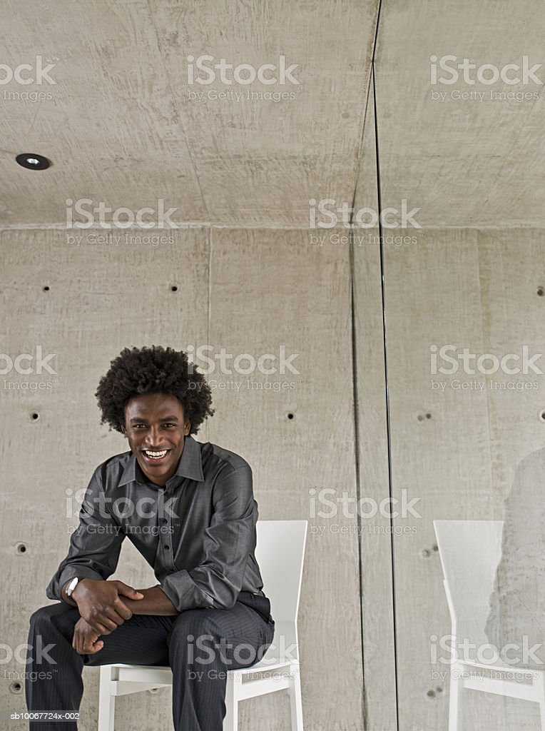 Well-dressed young man on chair near window, portrait foto de stock libre de derechos