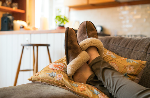 Close-up of a woman's feet in cosy slippers as she relaxes on the sofa at home.