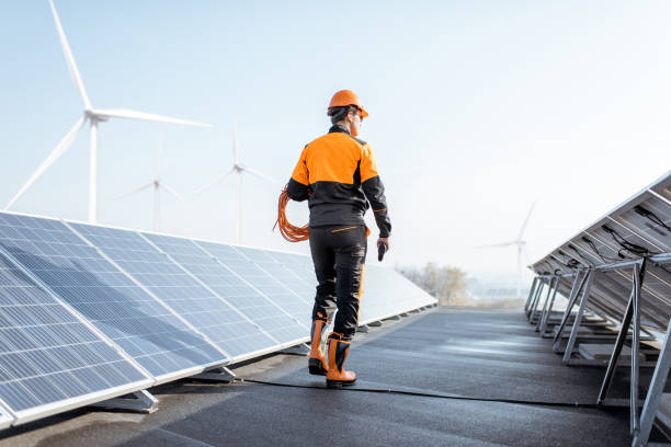 Well-equipped workman on a solar station stock photo