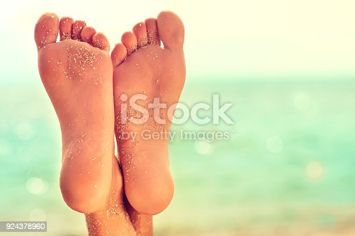 694409862 istock photo Well-groomed crossed woman's feet covered by sand. Pedicure, feet care and Spa. 924378960