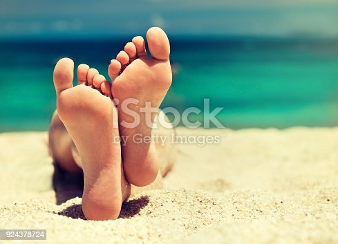 694409862 istock photo Well-groomed crossed woman's feet on the sand. Pedicure and spa treatment. 924378724