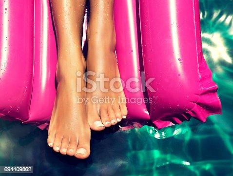 694409862 istock photo Well-groomed feet lay on the purple  swimming mattress. 694409862