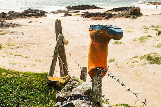 Wellington boot over a fence at a beach stock photo