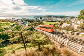 Aerial view over the city of Wellington, New Zealand, with a cable car climbing up the hill in the middle.