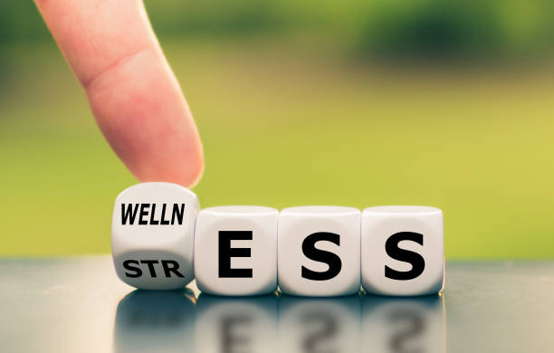 """Wellness instead of stress. Hand turns a dice and changes the word """"stress"""" to """"wellness"""". Wellness instead of stress. Hand turns a dice and changes the word """"stress"""" to """"wellness"""". wellbeing stock pictures, royalty-free photos & images"""