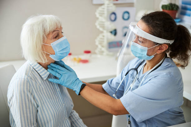 Well-protected physician is doing a neck palpation stock photo
